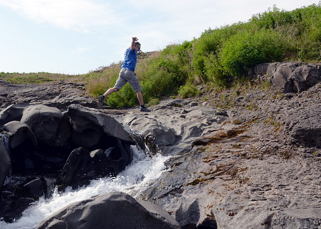 Sean jumping off rocks at a river and waterfalls in northern Iceland